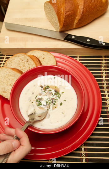 Cream Of Mushroom Soup In A Red Bowl On A Red Plate Garnished With Sliced Mushrooms