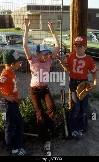 1975 three eight year old boys together with baseball equipment and hats leaning against a fence - Stock Image