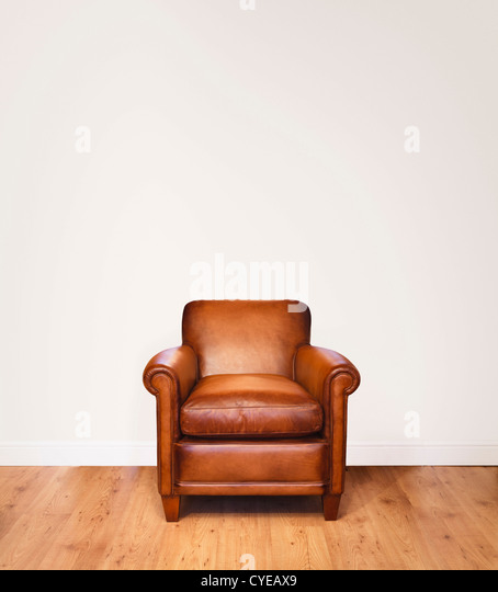 Leather Armchair On A Wooden Floor Against A White Background With Lots Of Space For Copy
