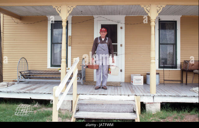 fisherman leaving his porch with tackle and rod in his overalls - Stock Image