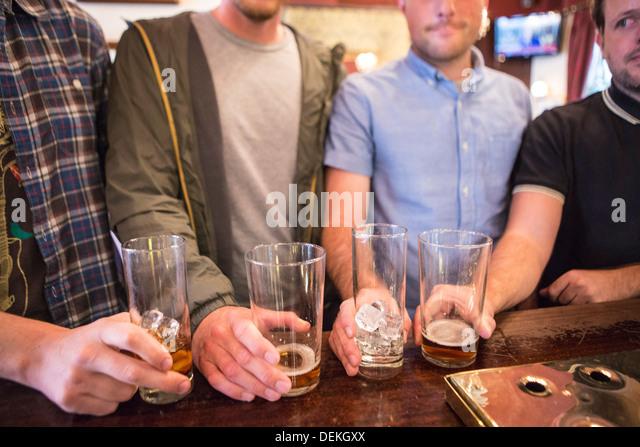 http://l7.alamy.com/zooms/f2e942c5e7ec4bbfb09e3174c65e3989/four-white-british-men-line-up-their-pint-glasses-on-a-bar-in-an-english-dekgxx.jpg