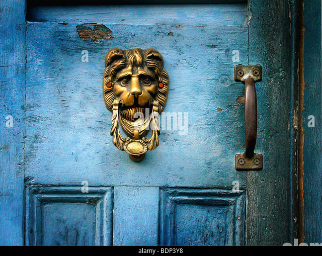 A brass door knocker on a blue door in the shape of a lions head - - Antique Brass Door Knocker Stock Photos & Antique Brass Door