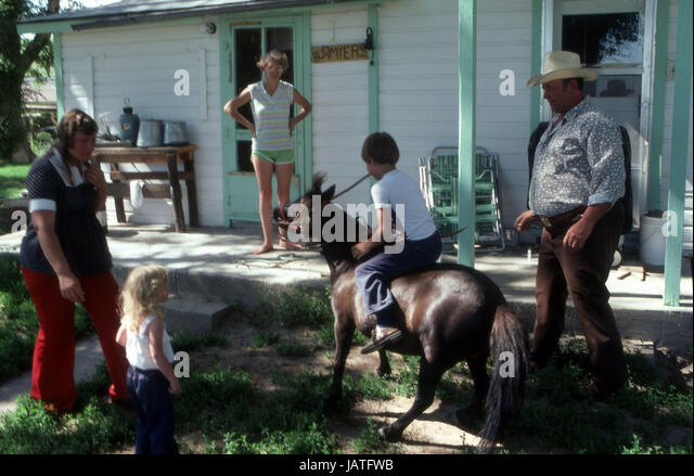 Young boy on a pony outside a farmhouse riding bareback in Nebraska as mother and father watches - Stock Image