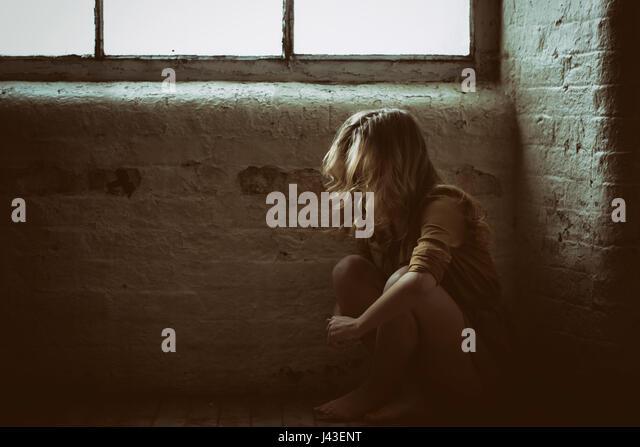 Sad bareffoted blondwoman sat on the floor by the window - Stock Image