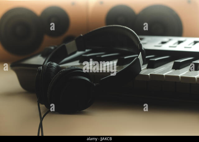 The headphones are on the synthesizer. The synthesizer stands on the background of the speakers. Front view - Stock Image