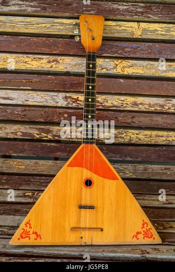 Musical instrument balalaika on wooden background - Stock Image