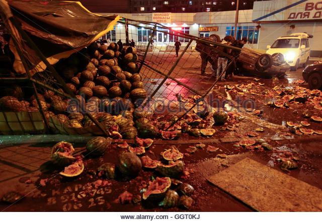 men-look-at-an-overturned-car-and-smashed-watermelon-stand-after-a-ggt0kj.jpg