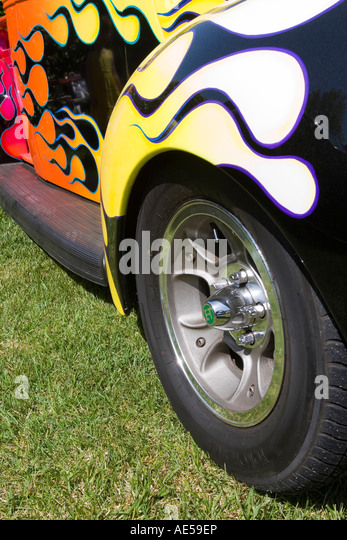 coloured flames paint job on a black ford pickup truck with wheels front headlight