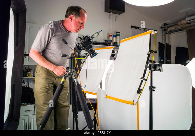 Commercial photography set including lighting stock photos photographer working on a commercial photography set including lighting background and grip gear aloadofball Images