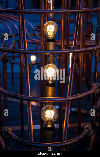 Incandescent light bulb between rusty pipes - Stock Image
