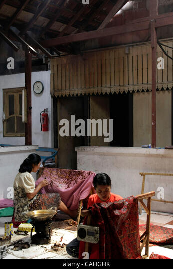 Solo, Indonesia January 18, 2008 Workers draw textile into a batik ...