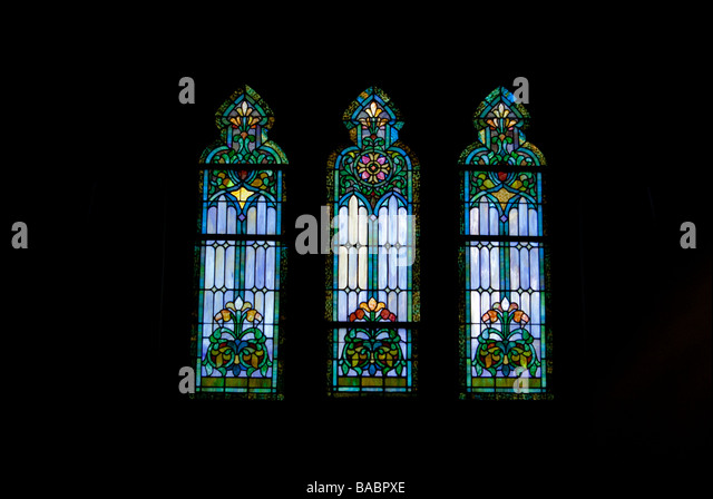 Three Restored Stained Glass Windows Lit From The Outside In A Church