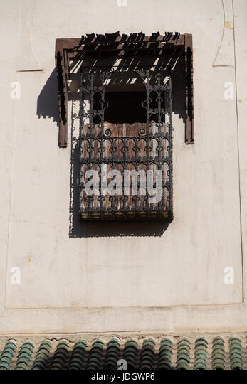 A balcony high on the wall of a Moroccan house, surrounded with ornate ironwork - Stock Image