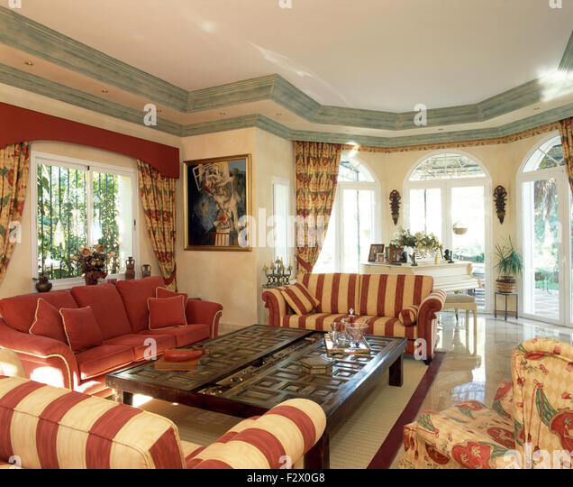 Lovely Red Striped Sofas Set Around Carved Wood Coffee Table In Living Room In  Large Spanish Villa
