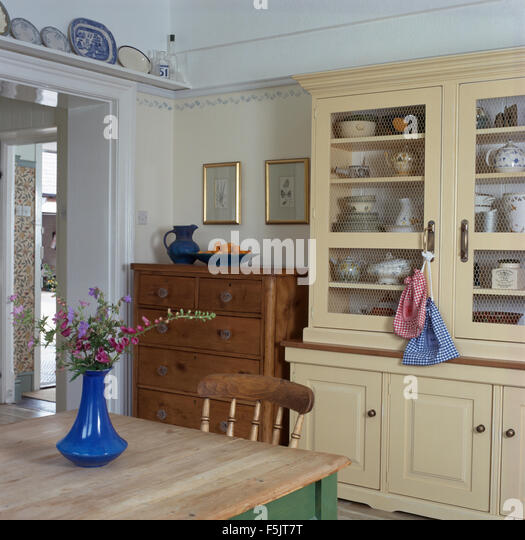 Cream Painted Dresser And Old Pine Chest Of Drawers In A Country Dining Room