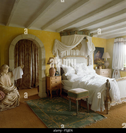 Bed with ornate canopy and white drapes and bedlinen in a yellow eighties bedroom with a & Large Canopy Bed Stock Photos u0026 Large Canopy Bed Stock Images - Alamy