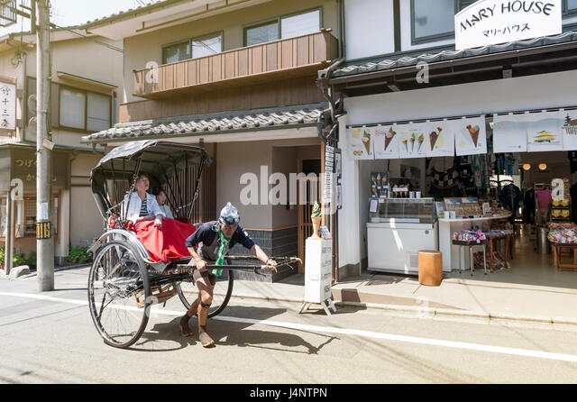 Kyoto, Japan - March 2016: Japanese traditional hand pulled rickshaw carrying tourists on Matsubara street in Kyoto, - Stock Image