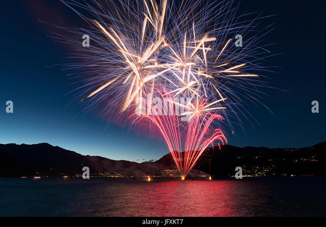 Fireworks on the lakefront of Luino over the Major Lake in a summer evening with blue sky and mountains in the background - Stock Image
