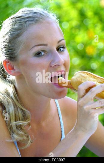 junge frau maedchen isst einen hot dog wuerstchen mit brot stock photo picture and royalty free. Black Bedroom Furniture Sets. Home Design Ideas