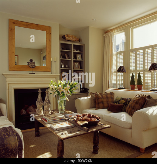 Nice Brown Cushions On Cream Sofa Below Window With Cream Plantation Shutters In  Living Room With Wood