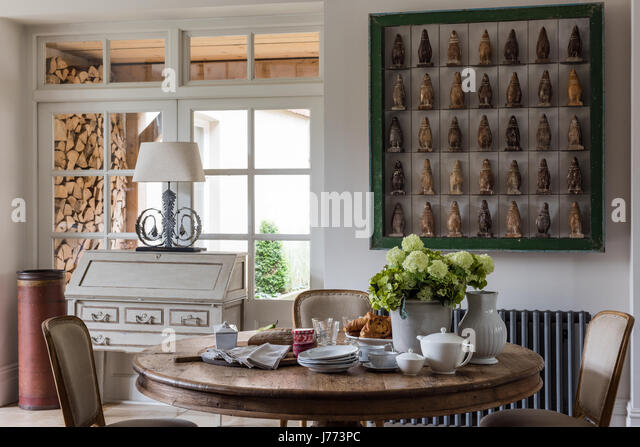 Penguin firgurines displayed in a bold green frame on wall of kitchen. The bureau, the lamp and the circular table - Stock Image