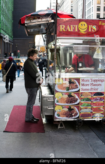 Male Customer Waits Patiently For His Order Under Overcast Sky At A Gyro Food Cart On