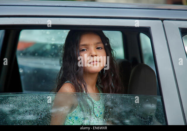 little girl looking out of the window stock photos