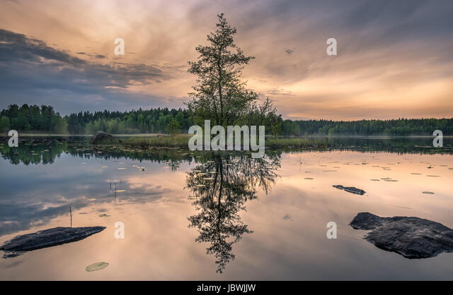 Scenic landscape with idyllic small island at summer night in National Park, Liesjärvi, Finland - Stock Image