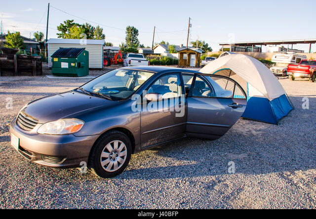 Car Parked With Camping Tent Behind In Trailer Campground On Rocky Floor
