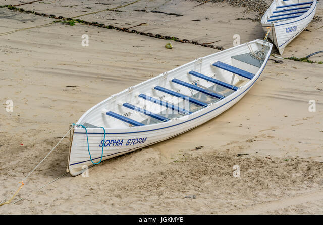 Two gig racing / rowing boatsin Newquay harbour, Cornwall. - Stock Image