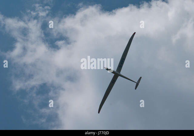 Sailplane, a glider designed for sustained flight, seen from below, up in the air in front of a cloud. - Stock Image