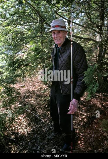 Senior man holding a fishing pole and smiling stock photo for Senior fishing license