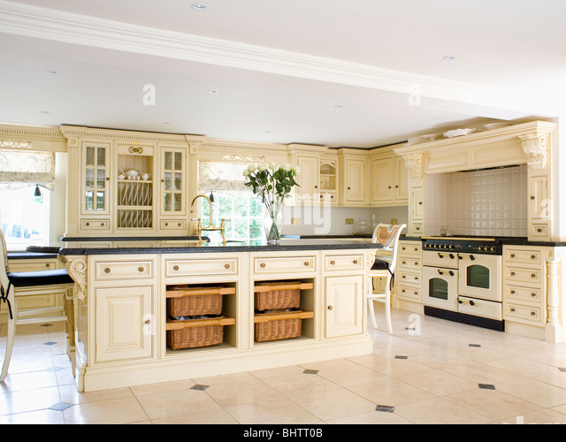 On Shelves On Island Unit In Large Cream Country Kitchen Stock Image