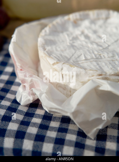 Camembert Cheese Round In Waxy Paper On A Blue Gingham Tablecloth.   Stock  Image