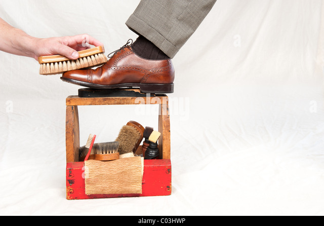 A man gets his shoes polished by a worker using a vintage shoe shine box -