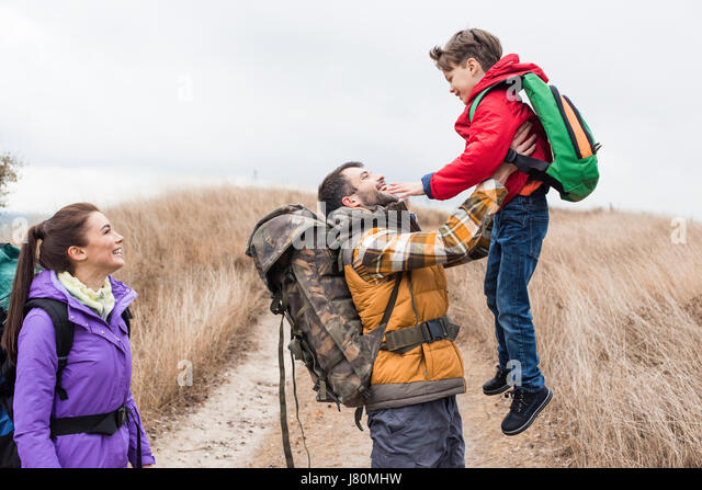 Side view of young smiling woman looking at happy father holding his little son - Stock Image