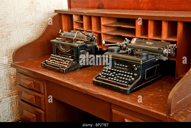 Two antique black typewriters are sitting on a vintage turn of the century  wooden desk, - Vector Vintage Typewriters Stock Photos & Vector Vintage