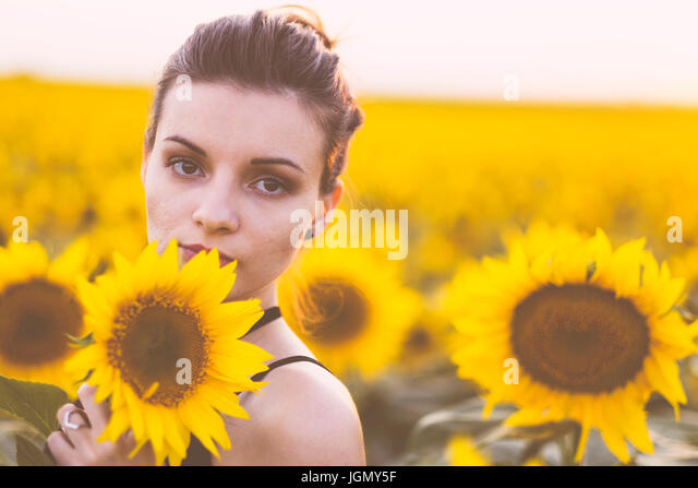 Beautiful natural young woman at sunflower field in summer sunset - Stock Image