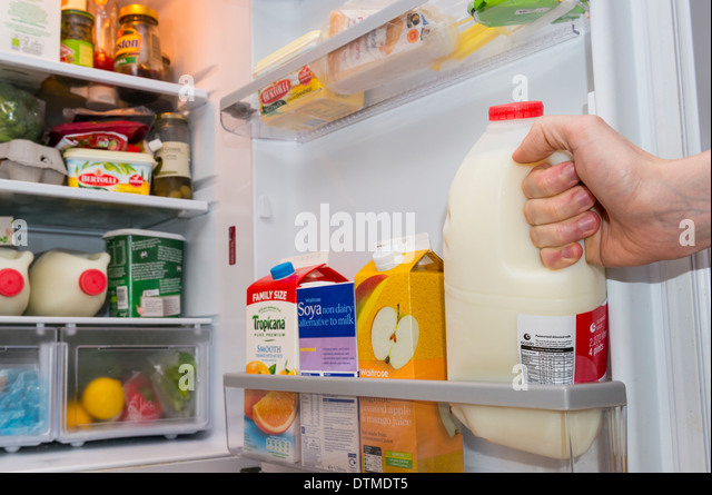 A hand pulling out a plastic bottle of milk from a well stocked fridge door - : fridge door - Pezcame.Com