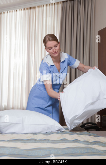 room maid fluffing up pillow stock image