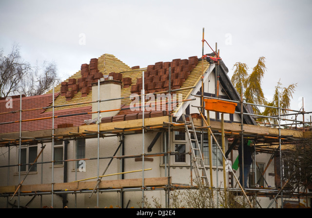 Lovely UK Workman Standing On Scaffolding Working On Re Roofing A Detached House    Stock Image