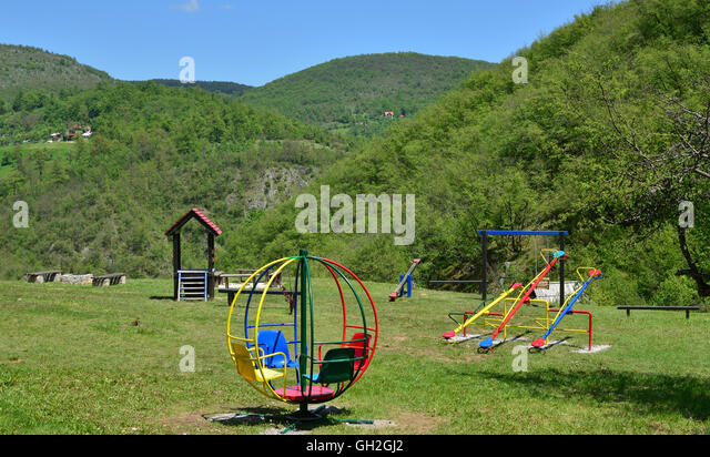 Children Playground With Merry Go Round Seesaws And Swings In Lush Mountain Landscape