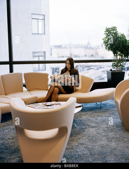 a woman reading the papaer in an office sweden stock image business nap office relieve