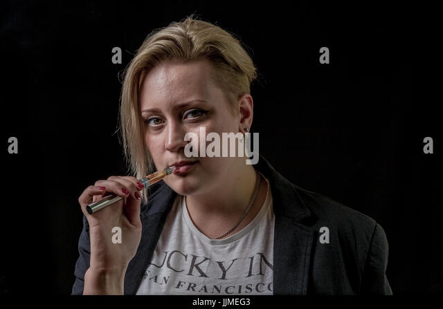 Woman holding electronic cigarette between her teeth - Stock Image