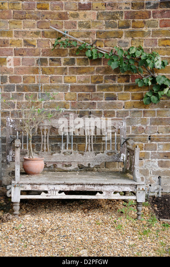Old Wooden Garden Bench In Front Of Brick Wall   Stock Image