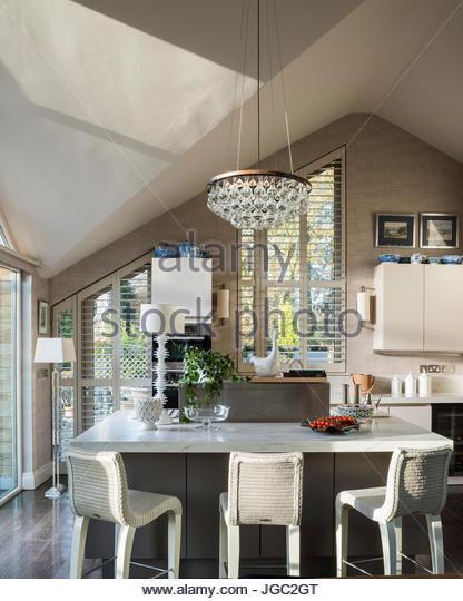 Lightbulb pendant above breakfast bar in A-frame kitchen - Stock Image