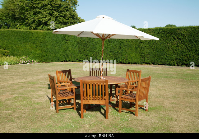 Garden table chairs and parasol on a summers day in Kent  UK   Stock Image. English Garden Garden Table Chairs Stock Photos   English Garden