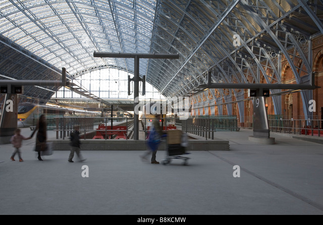 Passengers cross in front of waiting Eurostar trains at St Pancras ...