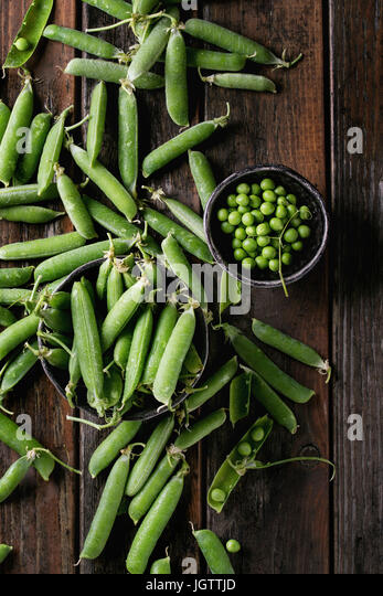 Young organic green pea pods and peas in bowls over old dark wooden planks background. Top view with space. Harvest, - Stock Image