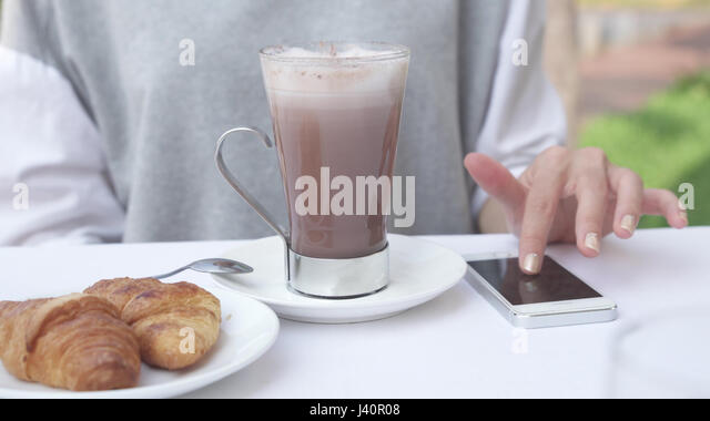 Young Woman Checks Notifications On Smartphone While Drinking Cacao With  Croissant. Female Use Mobile Phone